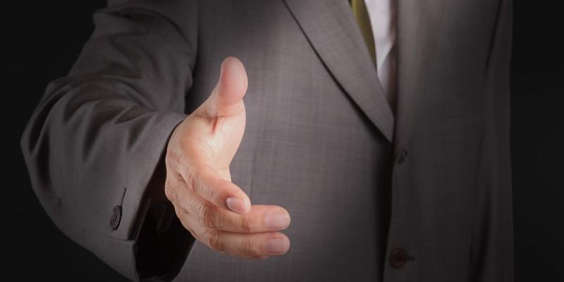 offering for handshake on dark background